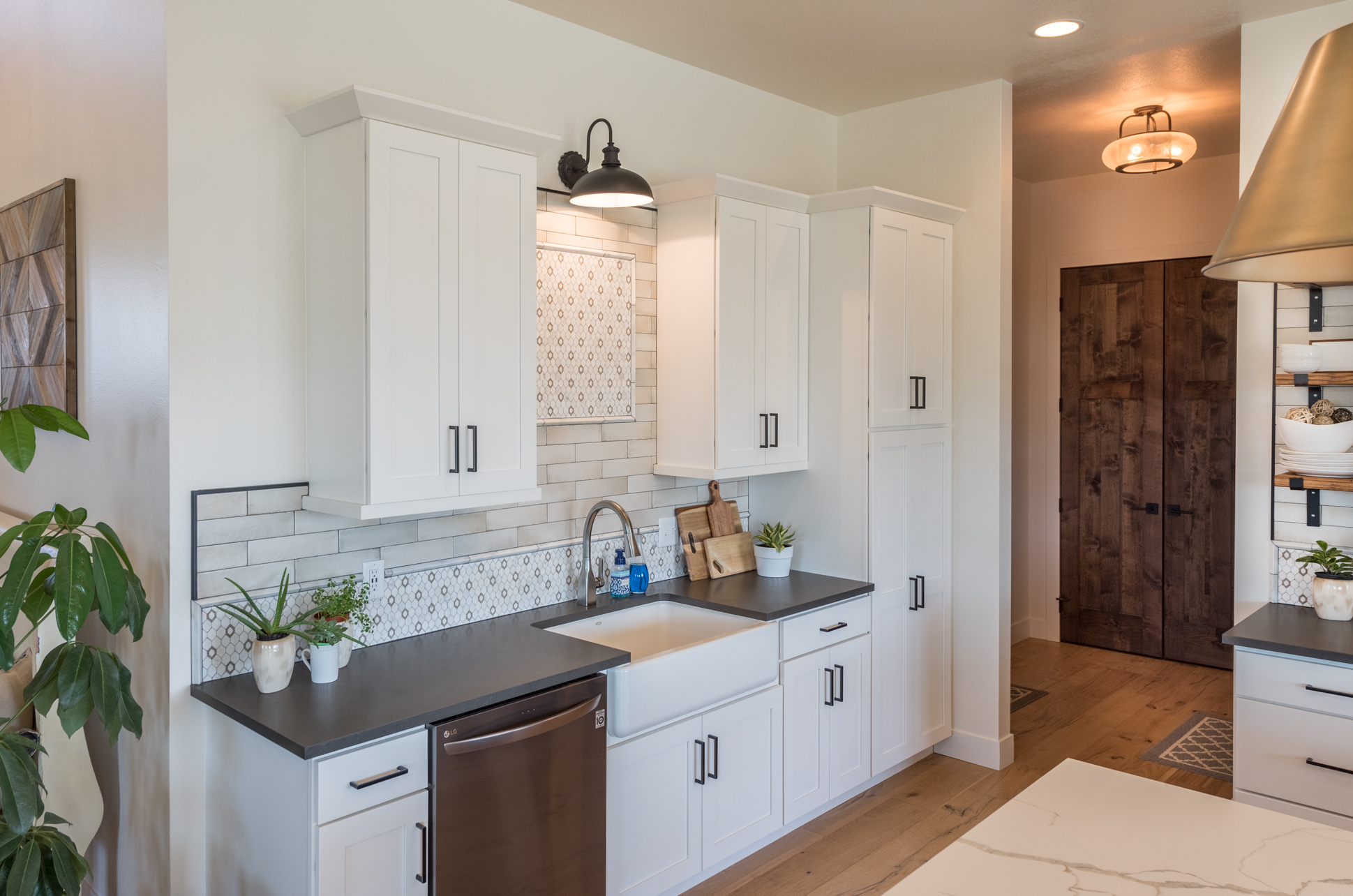 Kitchen with white cabinetry, farmhouse sink and island