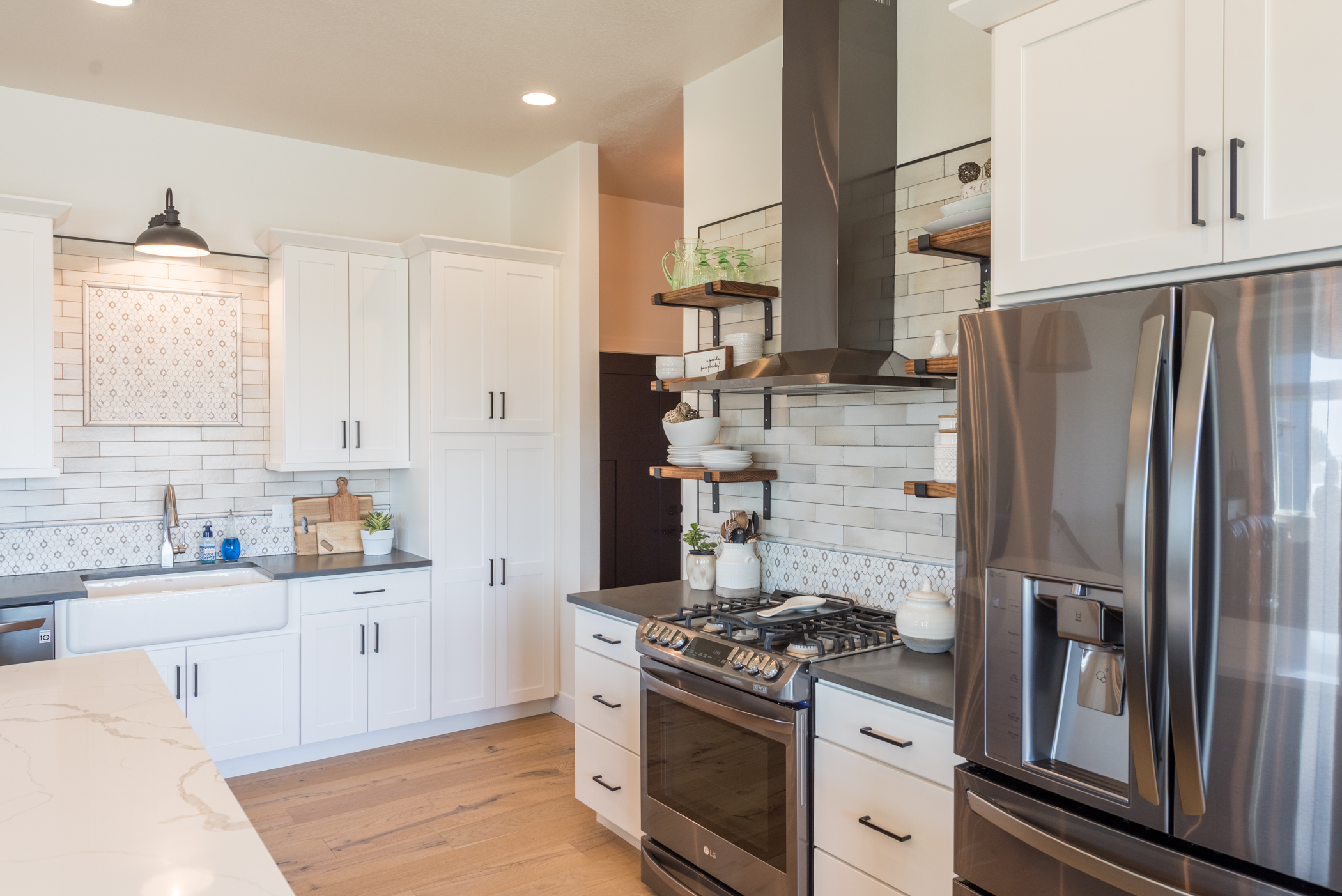 Kitchen with white cabinetry, tile backsplashes, stainless steel appliances with oven hood